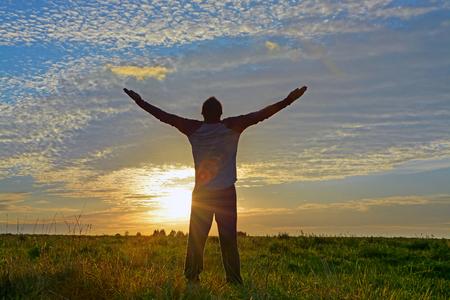 Silhouet van een man met opgeheven handen genieten van zijn vrijheid. Concept voor de godsdienst, verering, vrijheid Stockfoto