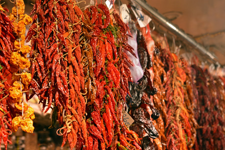 la boqueria: Rows of different chili peppers hang for sale at a fruit and vegetable market stall, , La Boqueria Market, Barcelona, Catalonia, Spain