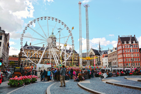 dam square: AMSTERDAM, NETHERLANDS - APRIL 17, 2016: Attractions park and tourists on Dam Square in Amsterdam, The Netherlands. The place is the historical center of the city with Royal Palace.