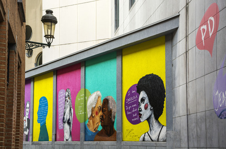 graffity: BRUSSELS - APRIL 21, 2016: Colorful graffiti with portraits of women and men on a wall of house in Brussels. Street art is very popular in the city Brussels