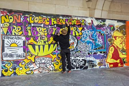 Graffiti: BRUSSELS - APRIL 21, 2016: Street art. Urban artist drawing colorful graffiti on a wall in Brussels.