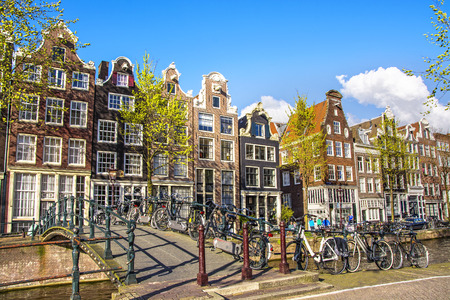 dutch: Traditional Dutch old houses and Bicycles parked on bridge in Amsterdam at sunny spring day. The Netherlands