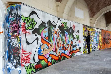street art: BRUSSELS - APRIL 21, 2016: Street art. Urban artist drawing colorful graffiti on a wall in Brussels.