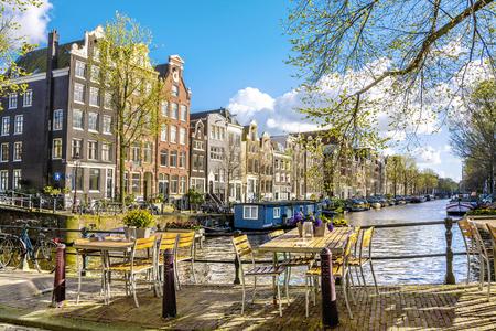 晴れた春の日にアムステルダムの運河沿いのカフェ。オランダ