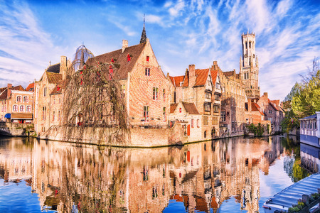 brugge: View of canal, tower Belfort and houses in medieval fairytale town Bruges at morning, Belgium
