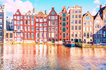 Traditional Dutch old houses on the canals in Amsterdam at sunny evening, Netherland. Stock Photo