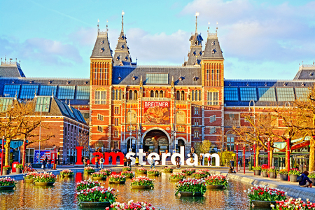 AMSTERDAM, Netherlands - APRIL 19, 2016: Rijksmuseum (National state museum) and city icon I Amsterdam slogan on Museumplein at sunset.