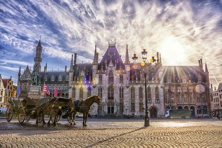 Horse carriages on Grote Markt square in medieval city Brugge at morning, Belgium. Stock Photo