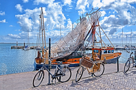 water town: Fishing trawler with nets on the water in Volendam Harbor - charming dutch fishing village, small town in North Holland near Amsterdam, Netherlands.