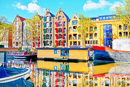 houseboat: Colorful old traditional Dutch house with shutters and houseboats are reflected in the water on the canals of Amsterdam, Netherlands