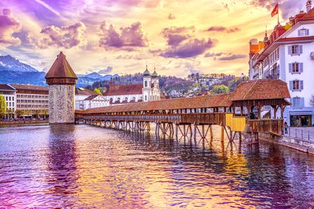 Oude overdekte houten Kapelbrug Kapellbrucke en Watertoren Wasserturm op de achtergrond van de met sneeuw bedekte Pilatusberg in het historische centrum van Luzern bij zonsondergang, Zwitserland