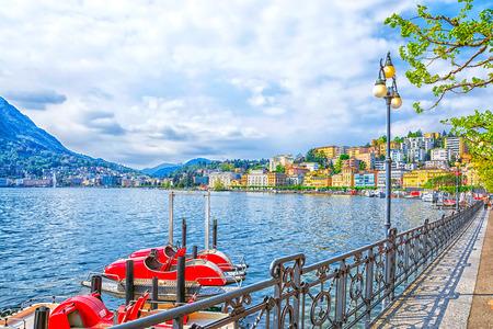 Promenade van luxetoevlucht in Lugano met het mooie landschap van Meer Lugano, dat door bergen van Alpen, het kanton van Ticino, Zwitserland wordt omringd.