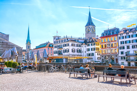People relax on benches and in a street cafe on the Limmat River quay in the background of old buildings and Fraumunster church on a sunny spring day, Canton of Zurich, Switzerland
