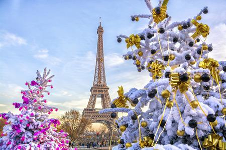 De Eiffeltoren is de belangrijkste attractie van Parijs op de achtergrond van versierde kerstbomen in december. Reizen wenskaart met Kerstmis in Parijs, Frankrijk