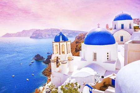 Hermosa puesta de sol en el fabuloso pueblo de Oia con casas blancas tradicionales y cúpulas azules de la iglesia en Santorini, Grecia Foto de archivo - 87873104