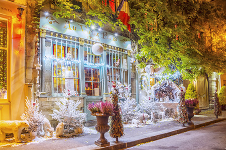 PARIS, FRANCE - DECEMBER 10, 2016: Typical Parisian cafes decorated for Christmas holidays on the narrow streets of Ile de la Cite in Paris, France