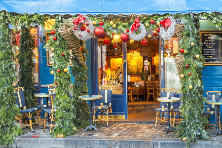 Typical Parisian cafes decorated for Christmas holidays in the artists quarter Montmartre in Paris at winter morning, France