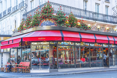 Typical Parisian cafe decorated for Christmas holidays in Paris at winter morning, France Editorial