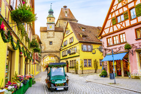 Touristic retro car on picturesque street, decorated for Christmas holiday in Rothenburg ob der Tauber, picturesque medieval historic town in Bavaria, Germany