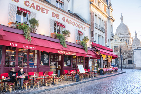 PARIS, FRANCE - DECEMBER 11,2016: View of the church of Sacre Coeur and typical street cafe in the Montmartre district in Paris