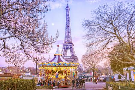 パリ、フランスの冬の夜のエッフェル塔とヴィンテージカルーセル。