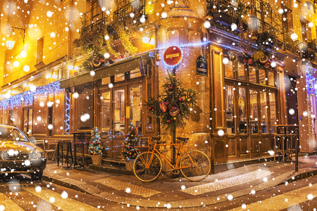 Typical Parisian cafes, decorated for Christmas holidays on a winter night in Paris, France. Editorial