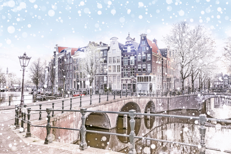 Traditional Dutch old houses and bridges on the canals in Amsterdam on a snowy winter night, The Netherlands Foto de archivo - 105090856