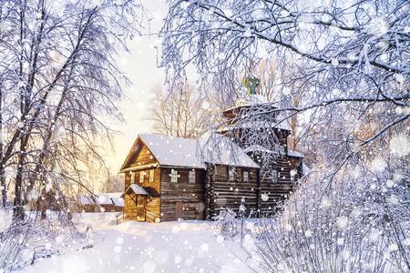 Belas paisagens com uma igreja de madeira em uma floresta de inverno cercada por árvores de neve congeladas e cobertas em um dia ensolarado e gelado na Rússia Foto de archivo - 89422716