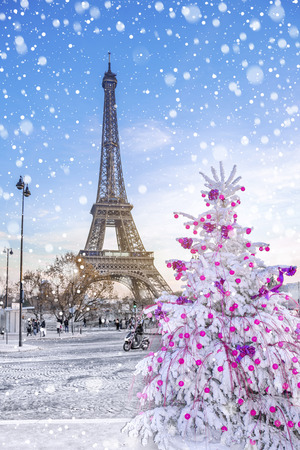 Eiffel Tower is the main attraction of Paris on the background of  Christmas trees covered by snow in winter. Travel Greeting Card from Paris with love, France