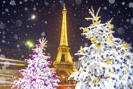 PARÍS, FRANCIA - 9 DE DICIEMBRE DE 2016: Demostración ligera del funcionamiento de la torre Eiffel en el fondo de los árboles de navidad adornados en diciembre por noche. Tarjeta de felicitación de viaje con la Navidad en París, Francia Foto de archivo - 90046733