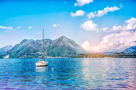 Beautiful landscape of the Alpine mountains on the Lago Maggiore lake against the background of a cloudy blue sky, ItalyBeautiful landscape of the Alpine mountains on the Lago Maggiore lake against the background of a cloudy blue sky, Italy