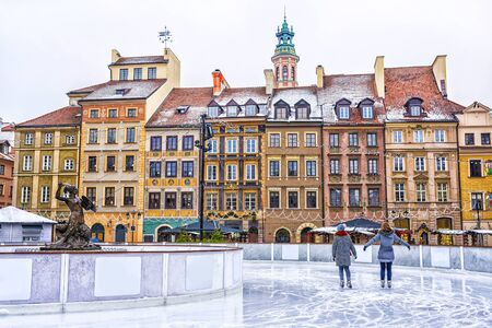 Two girls skate on a skating rink in the Old town square in Warsaw on the eve of Christmas, Poland