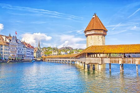 Ancient covered wooden Chapel Bridge Kapellbrucke and Water Tower Wasserturm in the historic center of Lucerne at sunset, Switzerland