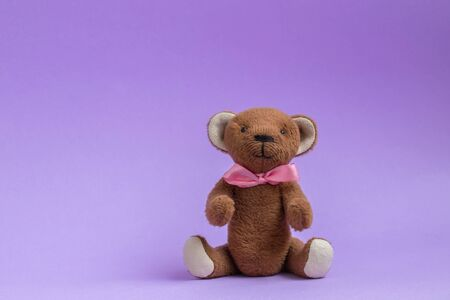 Teddy bear sitting on purple background. Teddy bear toy with pink bow. Copy space, postcard. Plush toy handmade.