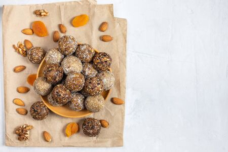 Homemade energy balls with dried apricots, raisins, dates, prunes, walnuts, almonds and coconut. Healthy sweet food. Copy space. Flat lay, top view.