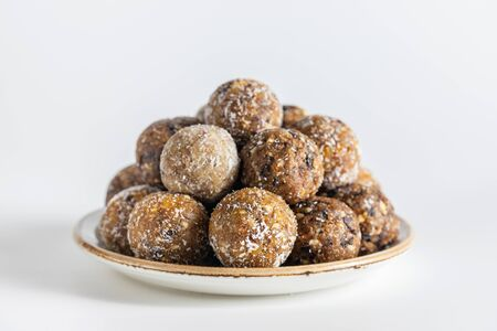 Homemade energy balls with dried apricots, raisins, dates, prunes, walnuts, almonds and coconut. Healthy sweet food. Energy balls in a plate on a white background.