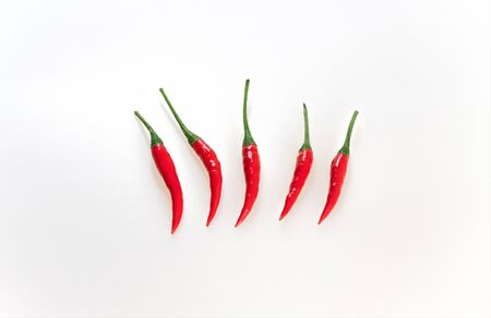 Red hot chili pepper on white background. Horizontal row of chili peppers, top view. Red ripe peppers with green stems with copy space. Spicy seasoning. Five chili peppers. Stock Photo