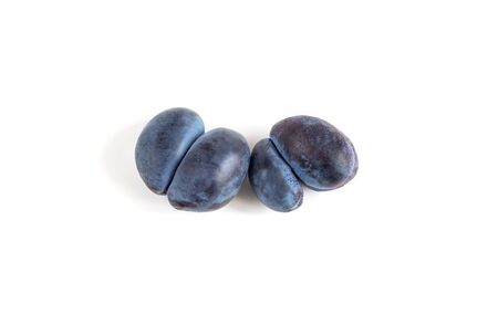 Trendy ugly food concept. Two purple plums on a white background. Fruit with a strange shape. The problem of food waste.