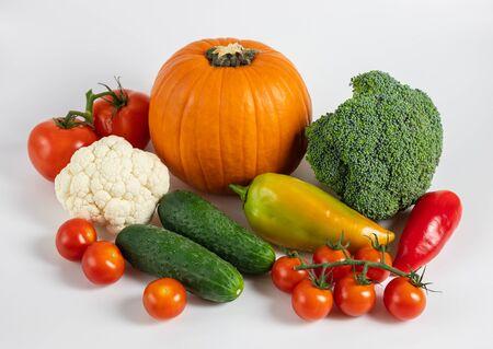 Concetto di cibo sano. Verdure su sfondo bianco. Bandiera. Raccolto autunnale con zucca, broccoli, cavolfiori, peperoni, cetrioli e pomodori.