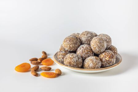 Homemade energy balls with dried apricots, raisins, dates, walnuts, almonds and coconut. Healthy sweet food. Energy balls in a plate on a white background. 版權商用圖片