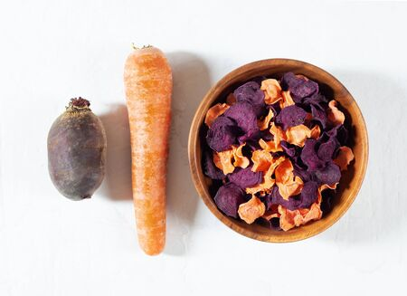 Dried carrot and beet chips in a wooden bowl and raw carrots, beets on a white concrete background. Organic natural food. Top view, flat lay.