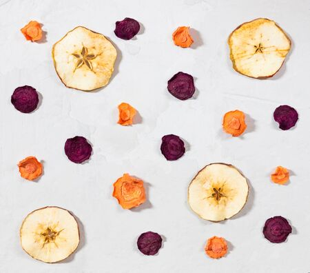 Dried carrot, beet, apple chips on a white concrete background. Organic natural food. Top view, flat lay. 免版税图像