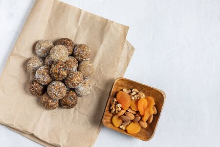 Homemade energy balls with dried apricots, raisins, dates, prunes, walnuts, almonds and coconut. Healthy sweet food. Flat lay, top view.