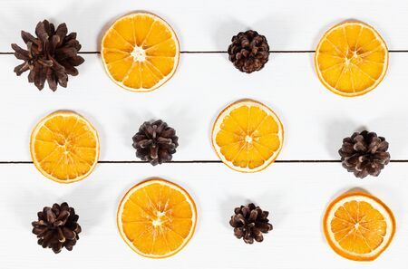 Christmas pattern with fir cones and dried orange slices on a white wooden background. Happy new year.