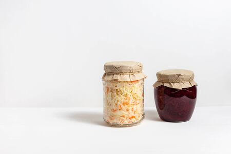 Homemade sauerkraut with carrots and cabbage salad with beets in a glass jar on a white wooden background. Fermented food. Copy space.