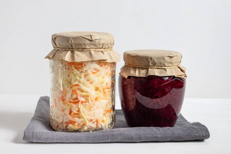 Homemade sauerkraut with carrots and cabbage salad with beets in a glass jar on a white wooden background. Fermented food.