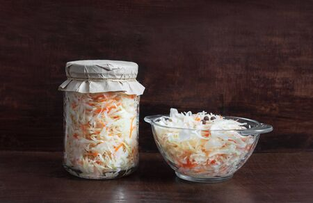 Homemade sauerkraut with carrots in a glass jar and bowl on a dark wooden background. Fermented food. Marinated vegetables.