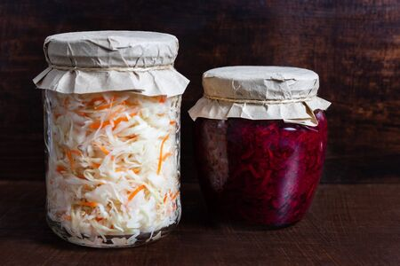 Homemade sauerkraut with carrots and cabbage salad with beets in a glass jar on a brown wooden background. Fermented food.