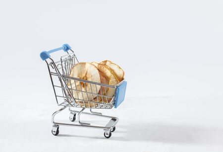 Dried apple chips in a toy grocery cart on a white background. Organic natural food. Concept vegan shopping. Copy space.
