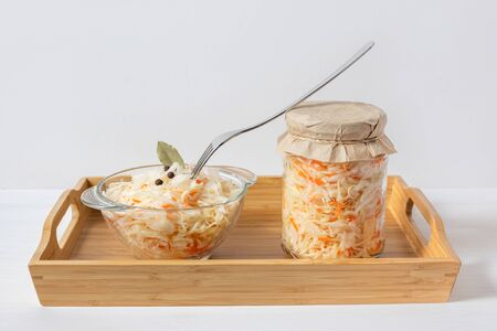 Homemade sauerkraut. Fermented food. Sauerkraut with carrots in a glass jar and bowl in a wooden tray on a white background.